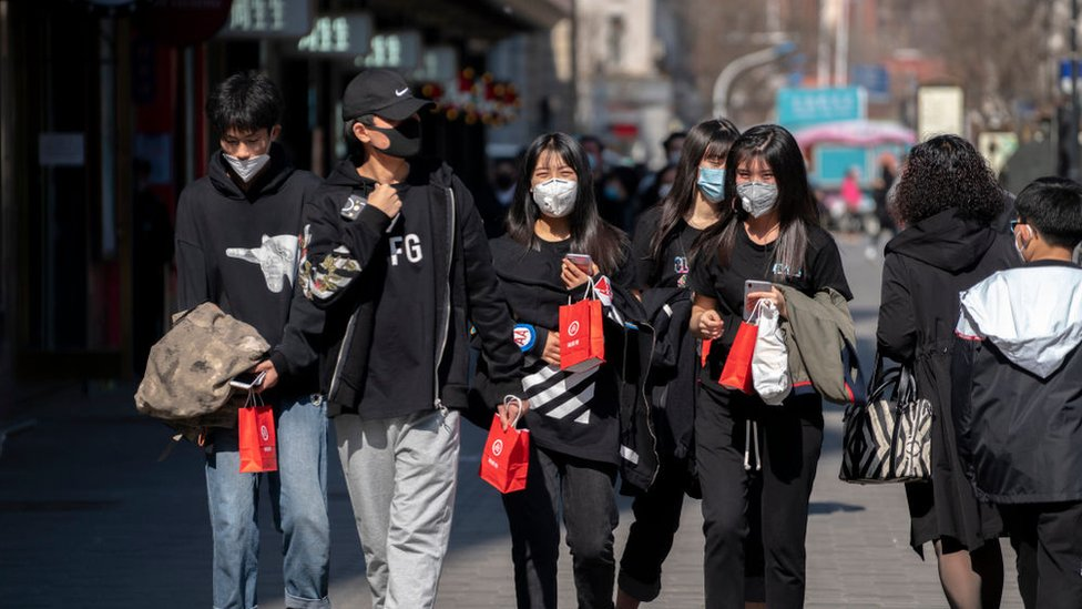 Jóvenes chinos con mascarillas.
