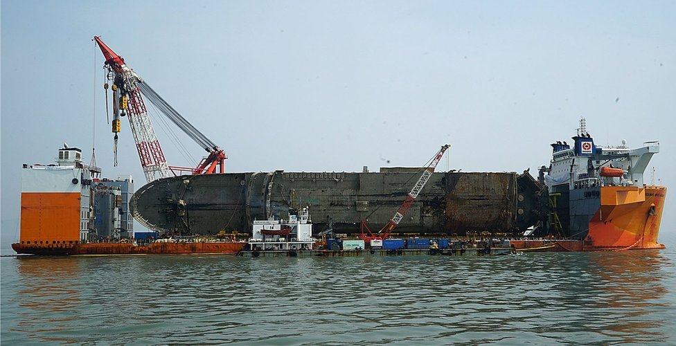 In this handout photo released by the South Korean Ministry of Oceans and Fisheries, the sunken ferry Sewol is seen on its side on a semi-submersible transport vessel during the salvage operation in waters off Jindo, South Korea, 28 March 2017.