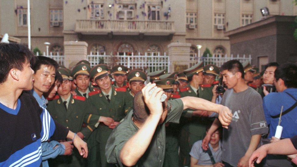 Un manifestante universitario lanza una piedra contra la embajada de EE.UU. en Pekín en mayo de 1999.