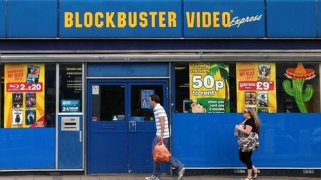 People walk past Blockbusters store