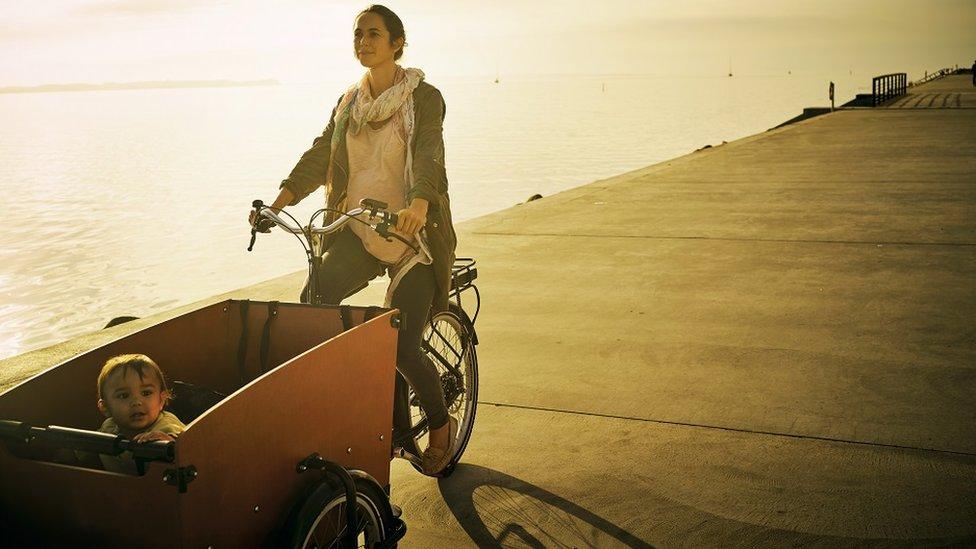 Una joven madre pedalea una bicicleta con su hijo en un carrito en frente