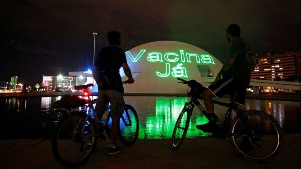 Duas pessoas em bicicletas diante de neon em que se lê vacina já
