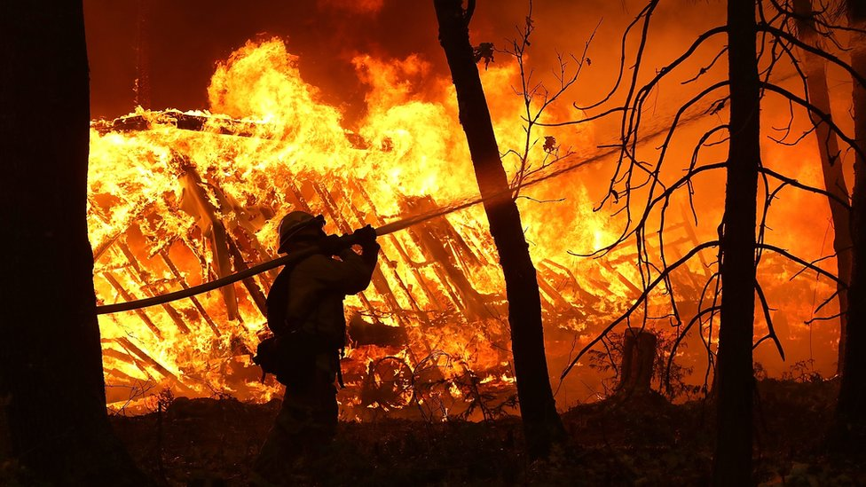 A Cal Fire firefighter sprays water on a home next to a burning home as the Camp Fire moves through the area on November 9, 2018 in Magalia, California