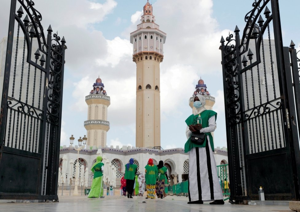 A woman stands with hand sanitiser at the entrance of the Great Mosque as hundreds of thousands of Senegalese Mouride Brotherhood pilgrims gather for the annual Grand Magal festival.