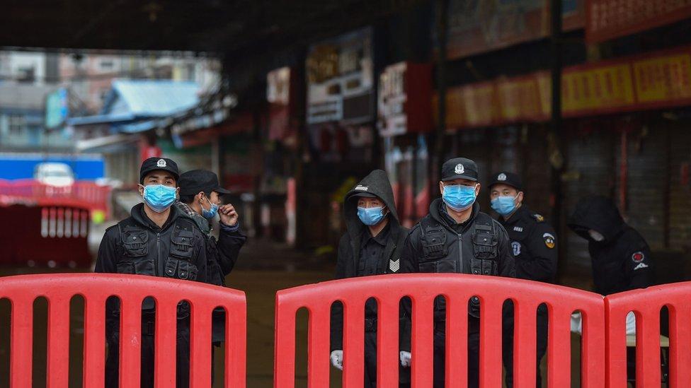Policías afuera del mercado de Huanan en Wuhan.