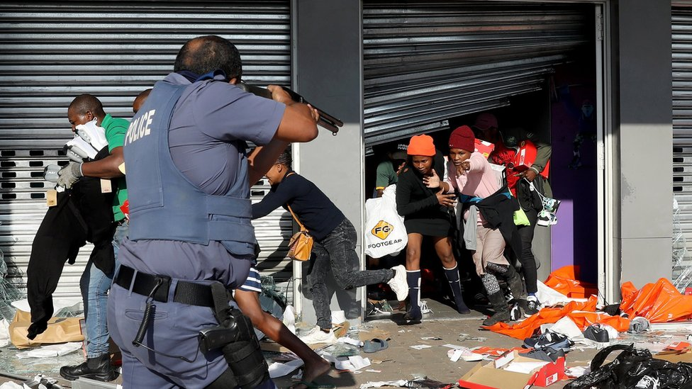 A member of the South African Police Forces tries to control looting during protests in Durban, South Africa, 12 July 2021.