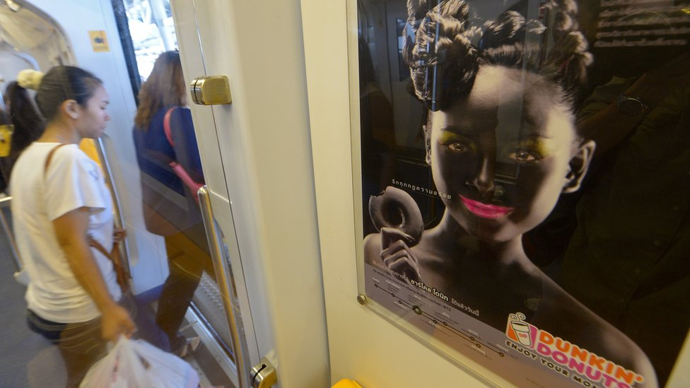 Thai passengers walk past a Dunkin' Donuts advertising campaign featuring a woman with black face make-up displayed at a skytrain station in Bangkok on September 3, 2013