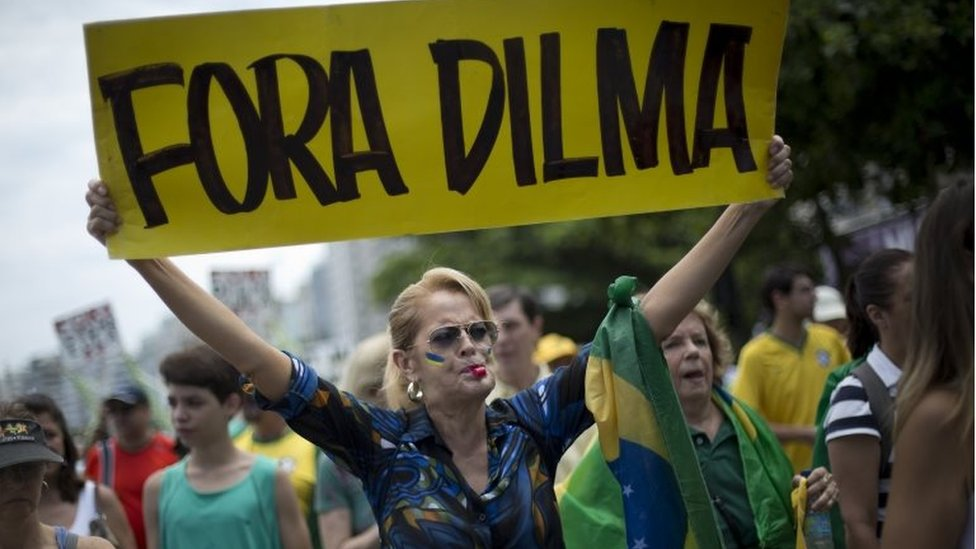 "In this Dec. 13, 2015 file photo, a woman holds a sign that reads in Portuguese; ""Dilma Out"" during a demonstration in favour of the impeachment of Brazil's President Dilma Rousseff, on Copacabana beach in Rio de Janeiro, Brazil. J"