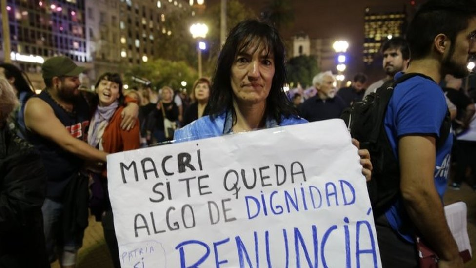 "A woman holds a sign that reads in Spanish ""Macri if you have any dignity, resign"" during a protest against President Mauricio Macri n Buenos Aires (07 April 2016)"