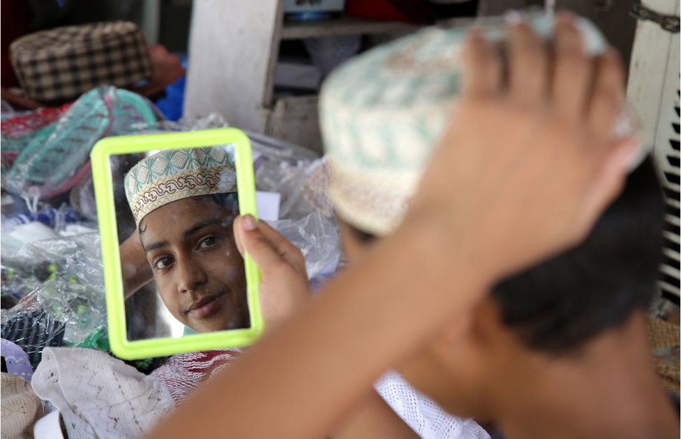 An Indian Muslim boy checks himself in a mirror as he buy prayer caps at a shop, prior to the Eid al-Fitr festival in Jammu, the winter capital of Kashmir, India, 14 June 2018