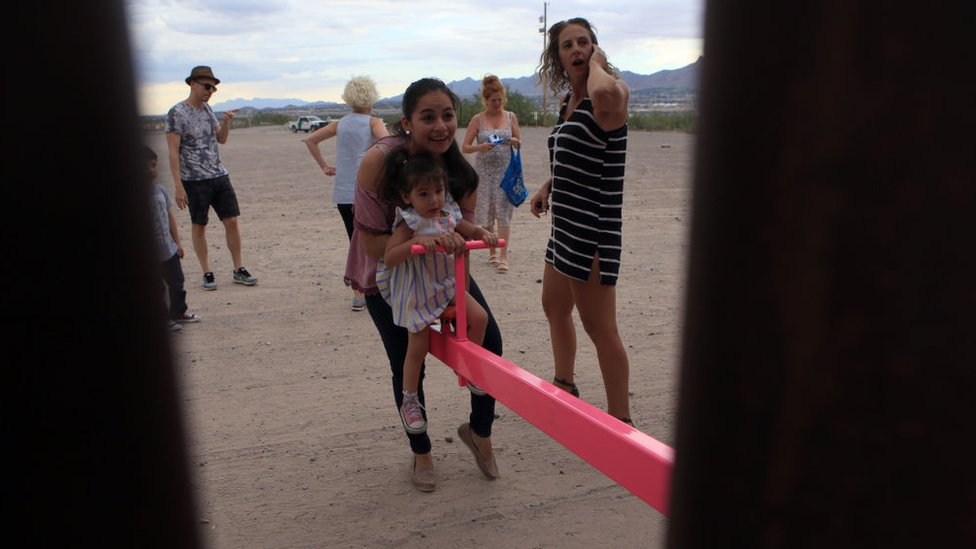 American and Mexican families play on seesaws over the Mexican border