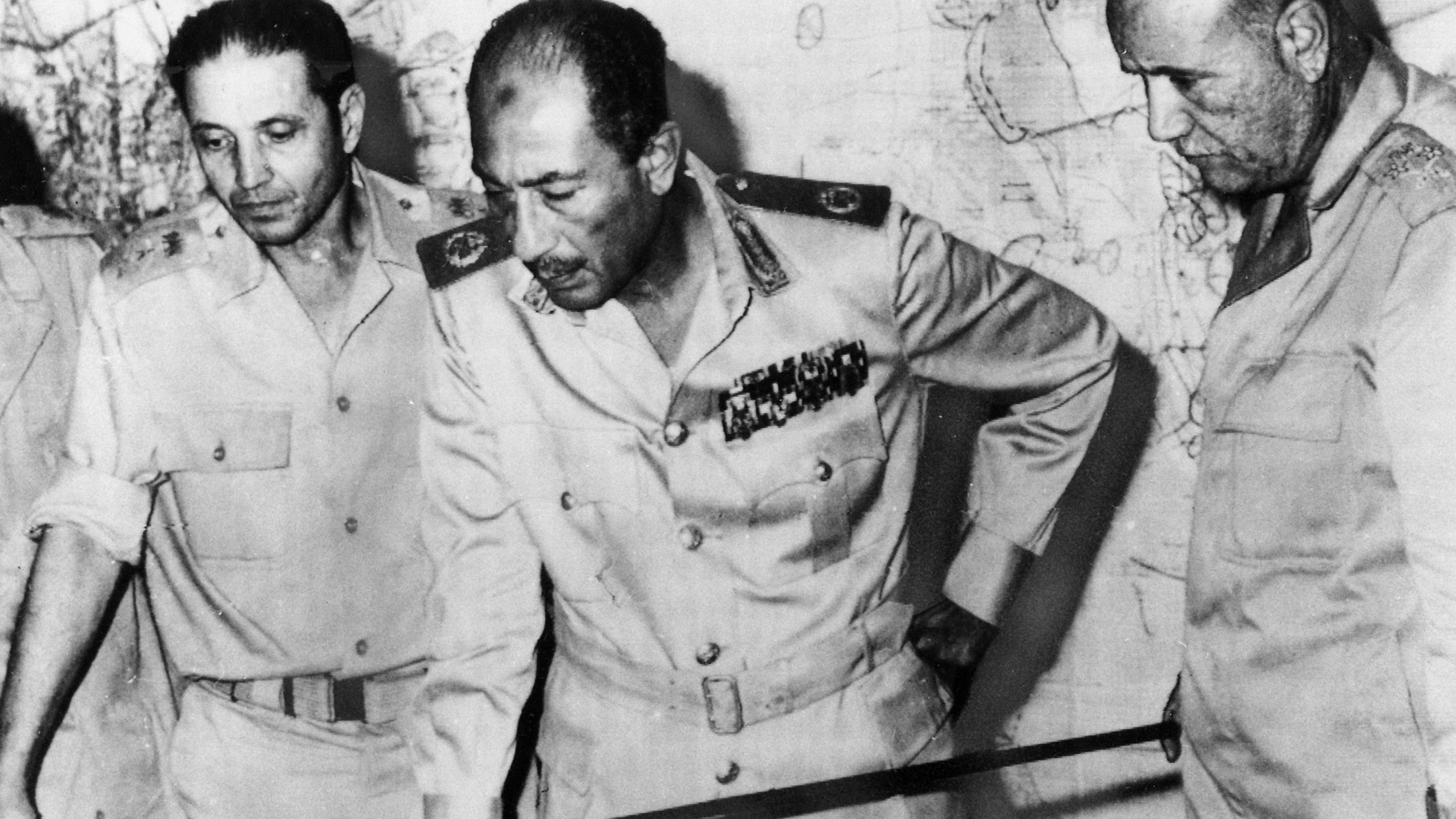 الرئيس السادات، في الوسط، وعلى يمينه سعد الدين الشاذلي، رئيس الأركان، وعلى يساره اسماعيل علي وزير الحربية، يتابعون من غرفة العمليات المركزية سير الحرب.