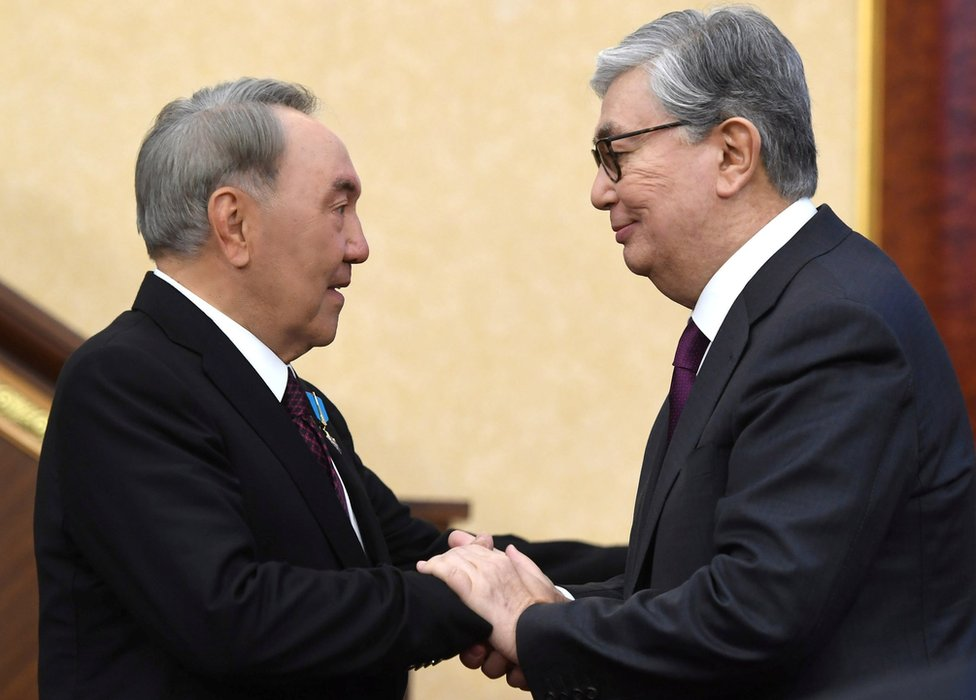 Acting President of Kazakhstan Kassym-Jomart Tokayev (R) shakes hands with his predecessor Nursultan Nazarbayev