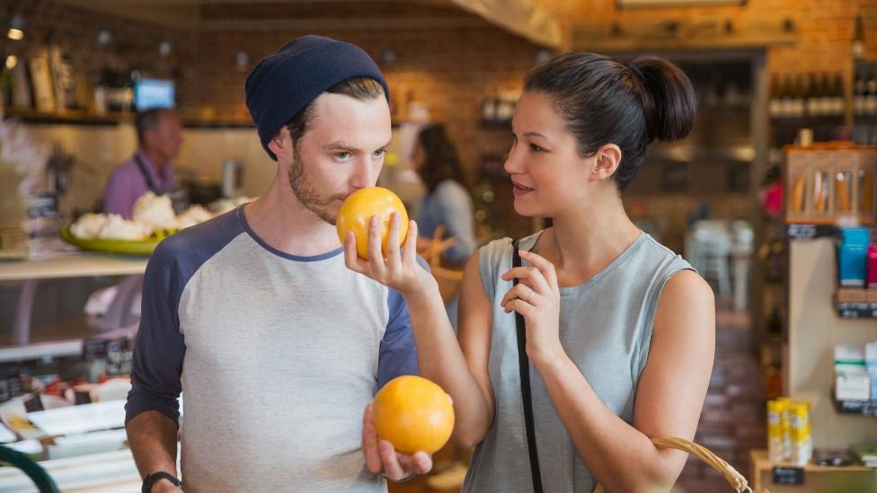 Casal cheirando frutas no mercado