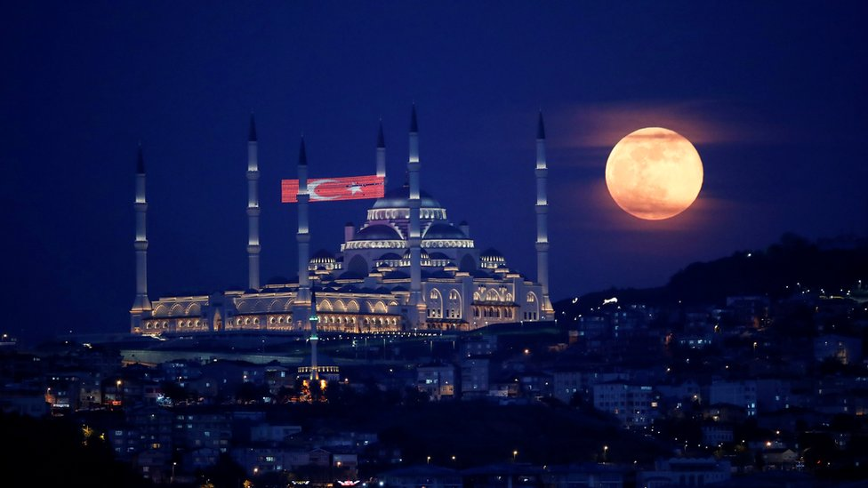 The full moon, also known as the Supermoon or Flower Moon, rises above the Camlica Mosque during the spread of the coronavirus disease (COVID-19), in Istanbul, Turkey