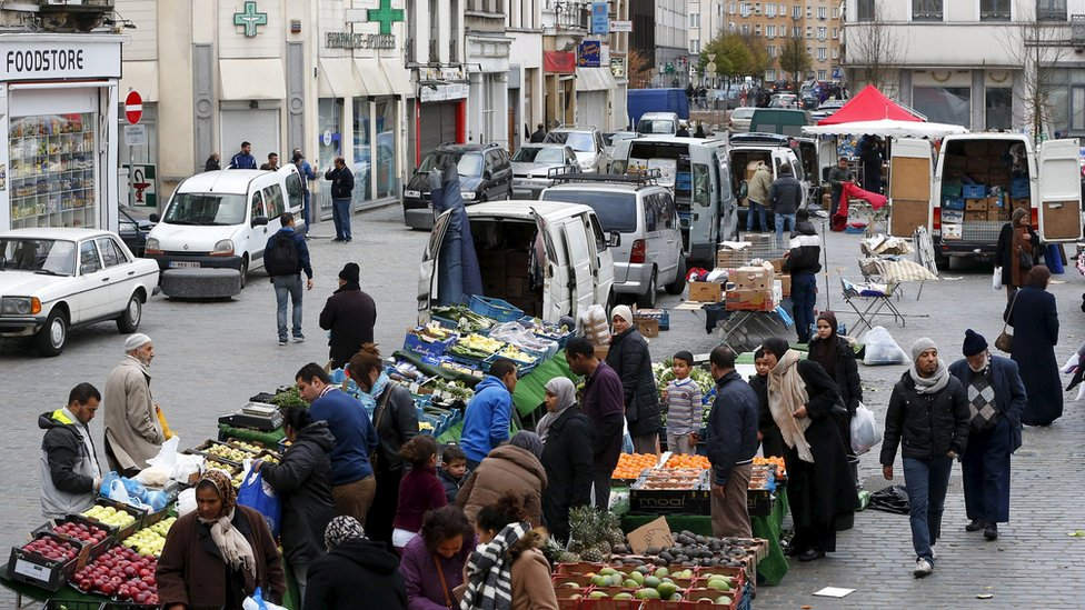 People shop at a market in the neighbourhood of Molenbeek, where Belgian police staged a raid following the attacks in Paris