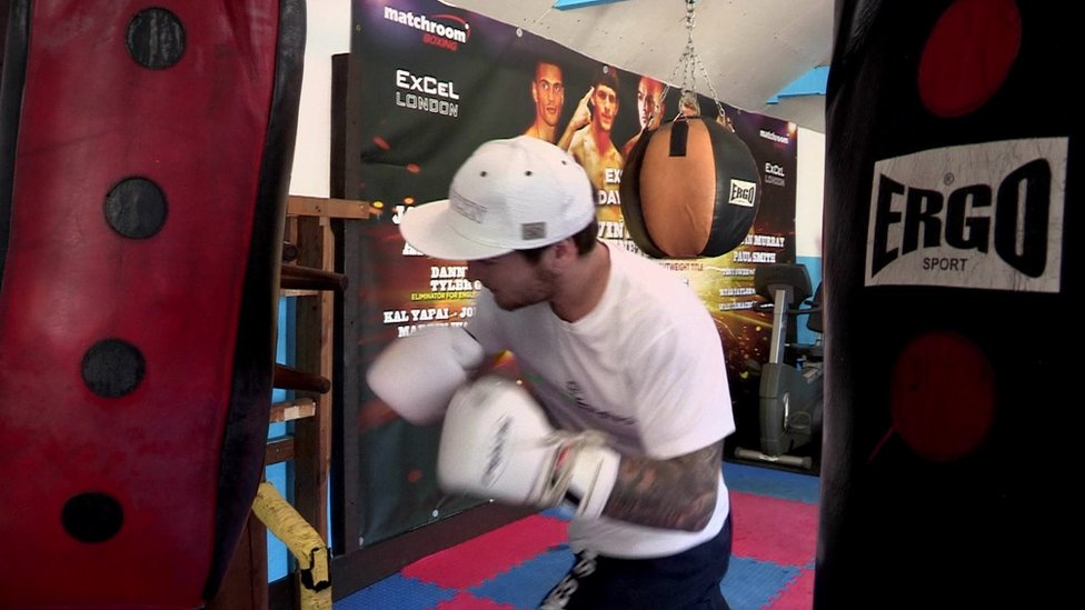 Boxer Carl Jones punches the heavy bag