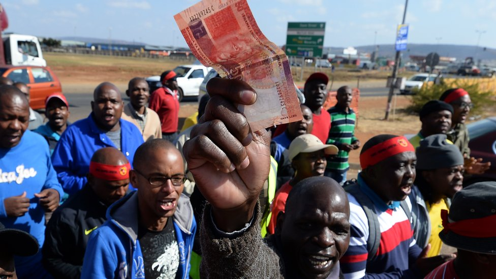 A factory work in South Africa holding up a banknote in Pretoria, South Africa - 2013