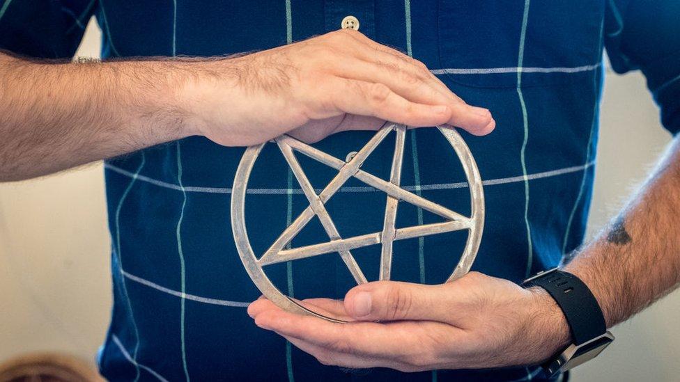 Manos de hombre sujetando una estrella de cinco puntas símbolo de la religión wicca