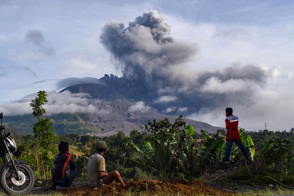 Villagers watch the eruption of Mount Sinabung