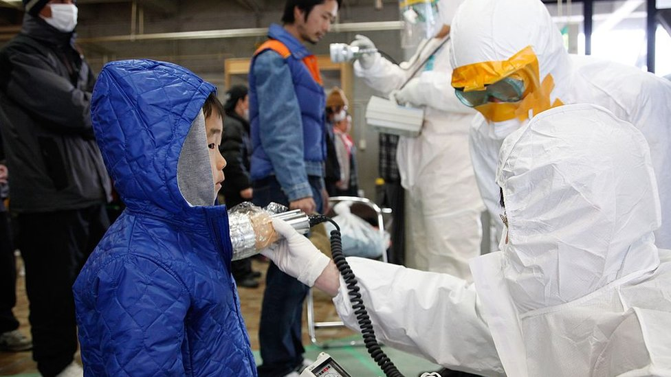 Workers check a boy for radiation near Fukushima, March 2011