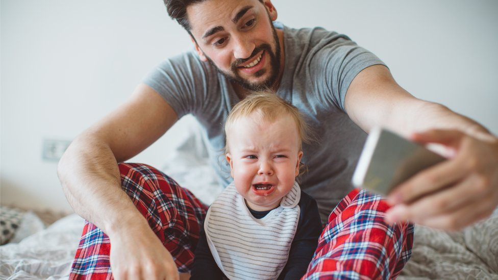A father takes a selfie with a crying baby