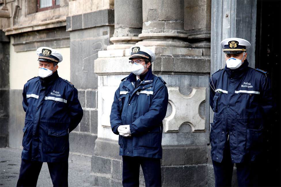 Three policemen stand in a line wearing face masks