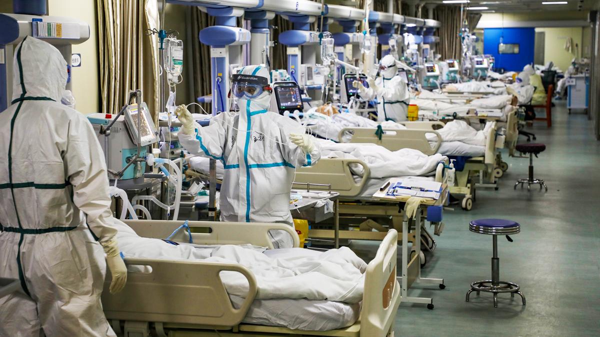 Медицинские работники в защитных костюмах с пациентами с Covid-19 в Ухане, Китай, 6 февраля 2020 г.