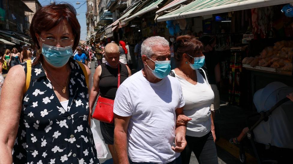 Pessoas andando nas ruas em Israel com máscara facial