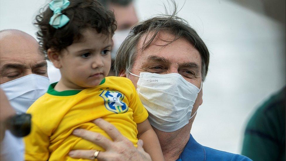 El presidente Jair Bolsonaro sostiene a una niña durante un rally en Brasilia, 17 de mayo 2020