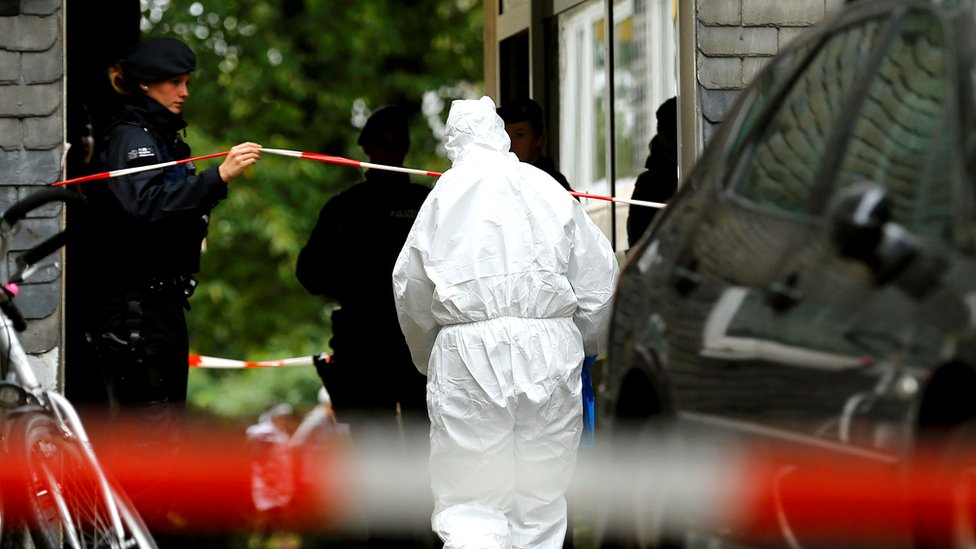 Police officers at the entrance of a residential building where the bodies of five children were found in the western town of Solingen, Germany