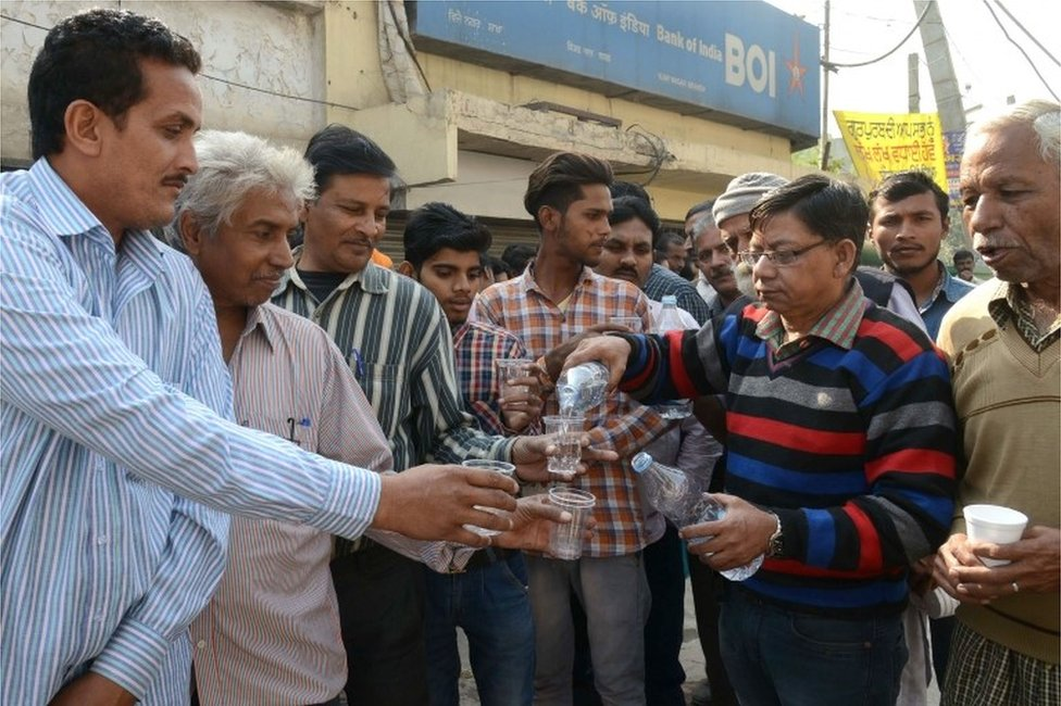 Indian volunteers distribute water to people, waiting in a queue to deposit and exchange 500 and 1000 rupee notes, outside a bank in Amritsar on November 16, 2016.