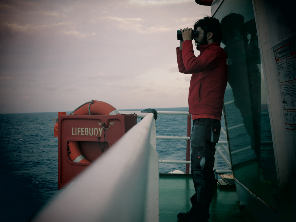 Volunteer looks out to sea through binoculars in daylight