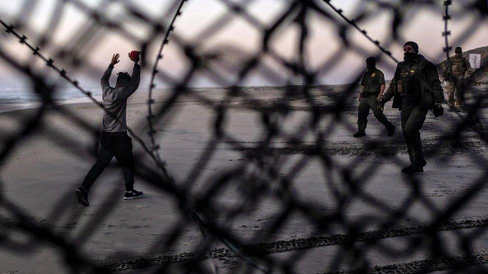 Un migrante se entrega a la Patrulla Fronteriza de Estados Unidos después de cruzar la valla en su frontera con México.