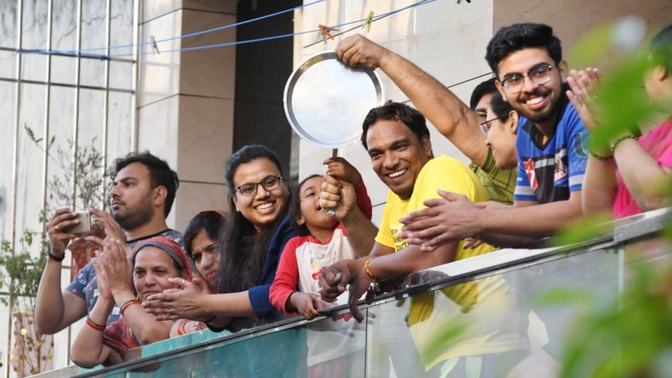 Indians bang utensils and clap from their balconies in New Delhi, India, 22 March 2020.