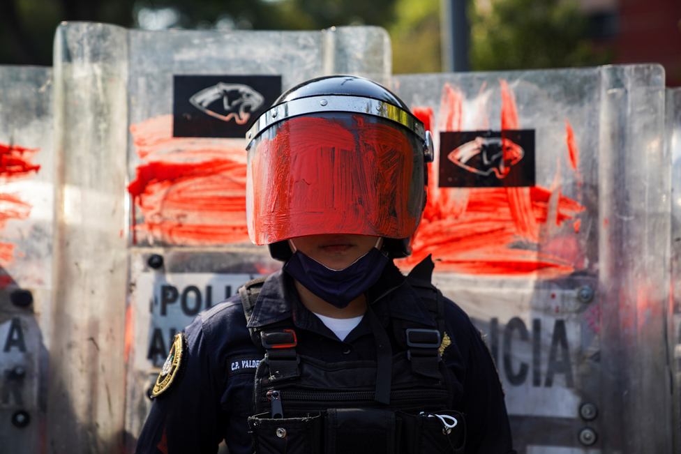 A riot police officer with her helmet visor painted red