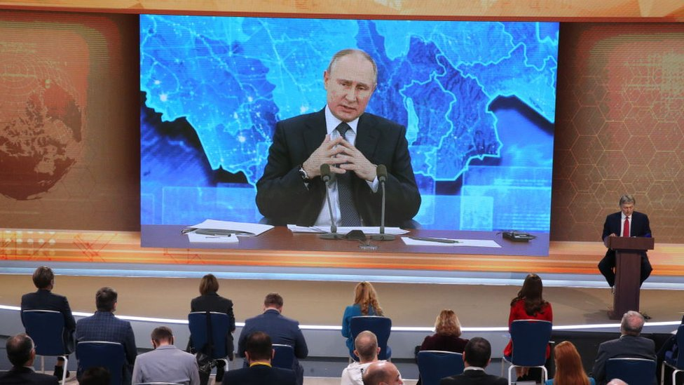 Vladimir Putin on a screen in front of an audience
