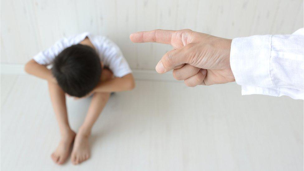 Niño con la cabeza bajada, con la mano de un adulto apuntándolo.