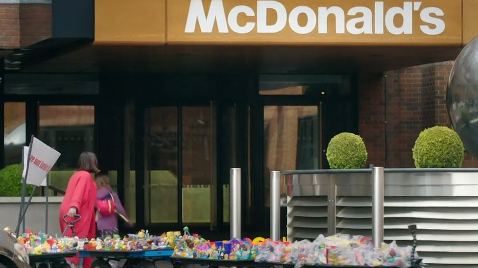 Ella and Caitlin McEwan at McDonald's headquarters with a trailer full of plastic Happy Meal Toys