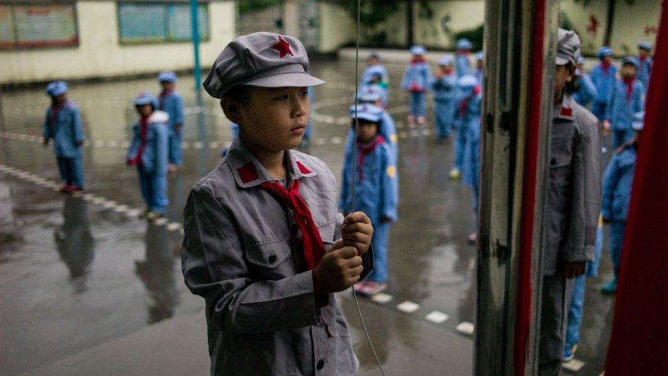 中國一所學校學生身著紅軍服裝升旗。