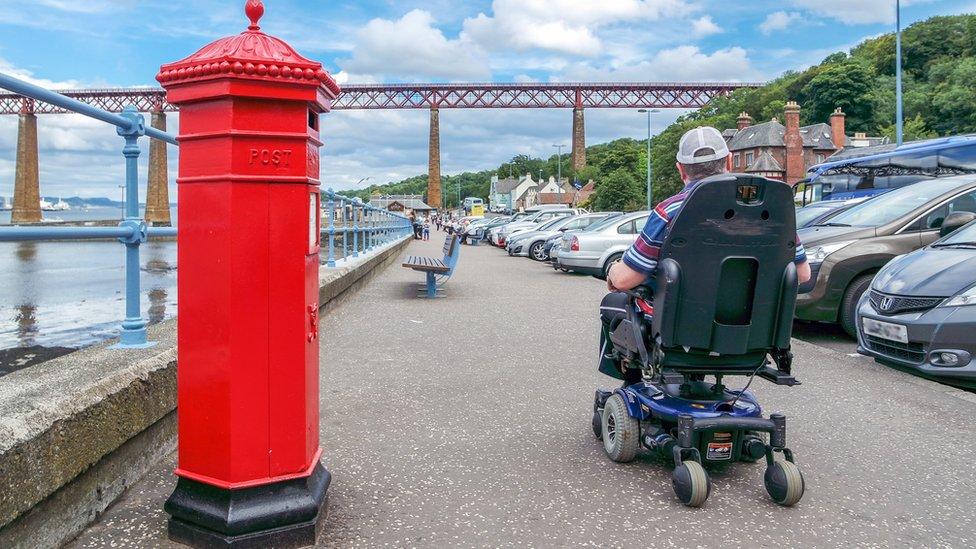 Man in wheelchair next to Forth Bridge