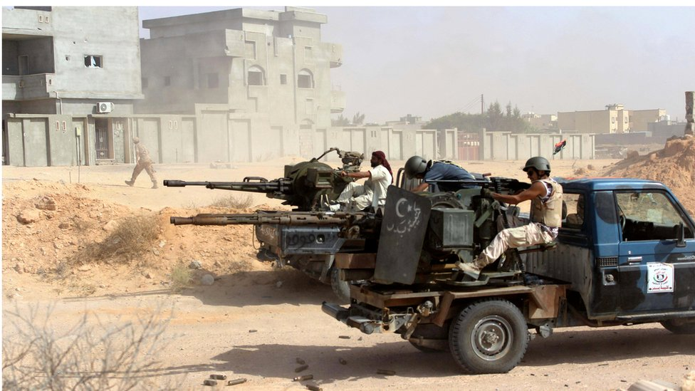 Fighters from forces aligned with Libya's new unity government fire anti-aircraft guns from their vehicles at Islamic State positions in Algharbiyat area, Sirte, June 21, 2016.
