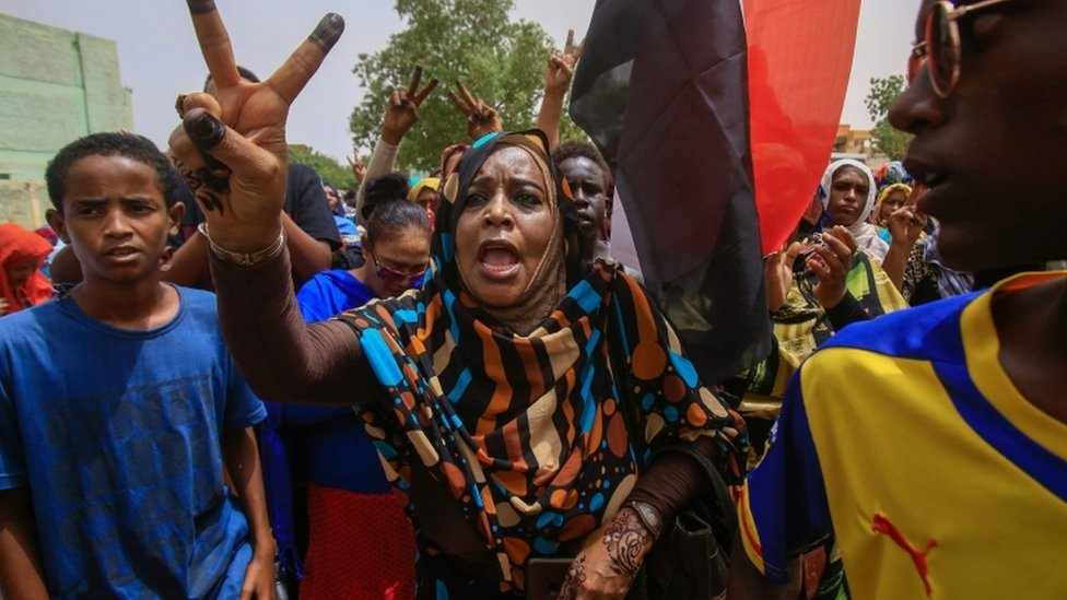 A Sudanese protesters flashes the V-sign during a mass demonstration against Sudan's ruling generals in Khartoum on June 30 2019