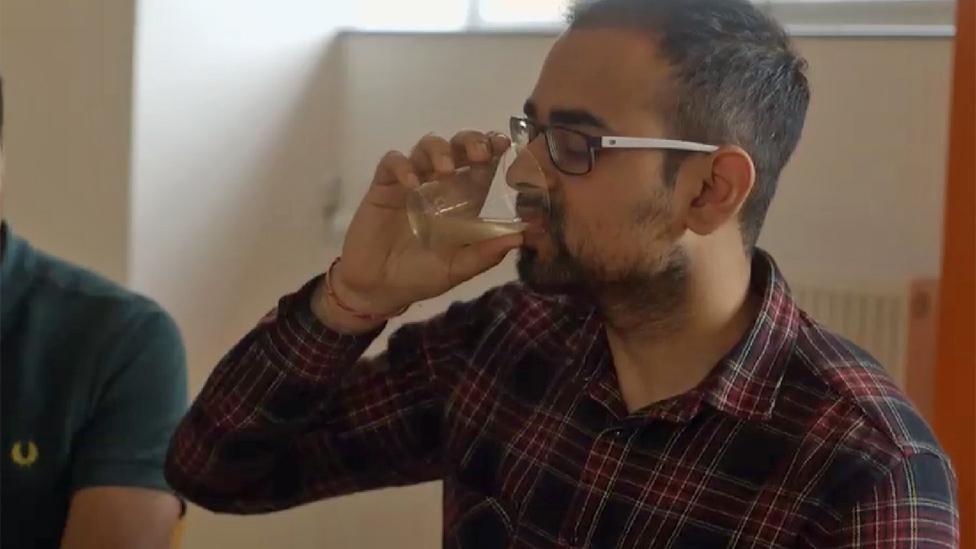 Volunteer drinking apple cider vinegar