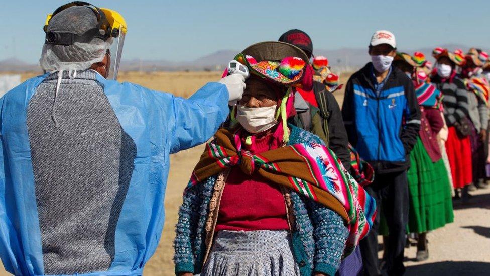 Personas hacen fila en Puno, Bolivia, para tomarse la temperatura.