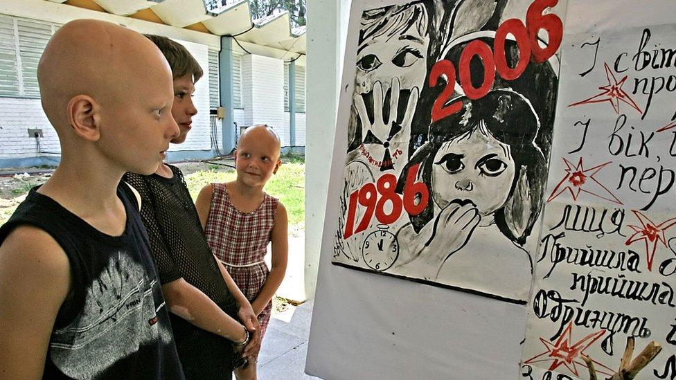 Varios niños miran una ilustración de recuerdo a las víctimas de Chernóbil