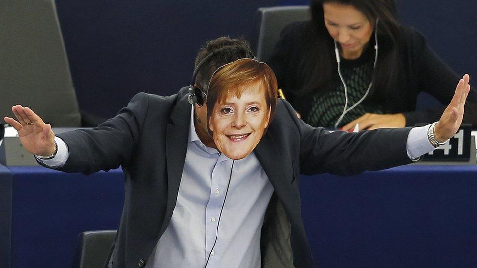 Italian Member of the European Parliament Gianluca Buonanno gestures as he wears a mask depicting German Chancellor Angela Merkel