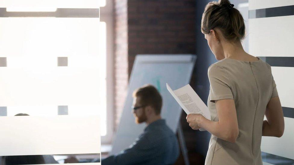 Una mujer con papeles en la mano mira a un colega hombre.