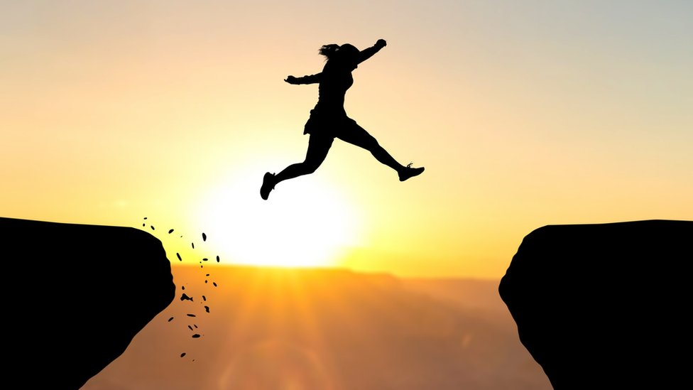 Mujer saltando entre dos rocas