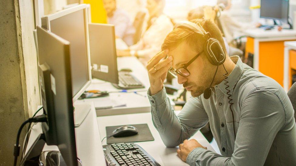 Hombre atiende una llamada de una línea telefónica de ayuda